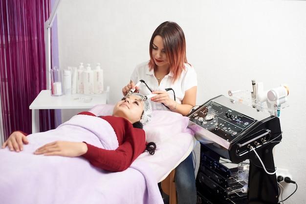 Bela morena jovem, obtendo a pele apertando o tratamento microcorrente por skincare terapeuta rejuvenescer mimos no escritório esteticista