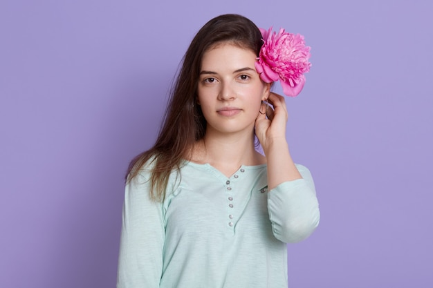 Bela morena jovem vestindo roupas casuais, segurando a flor de peônia rosa atrás da orelha