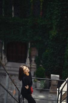 Bela morena posando em uma escadaria preta