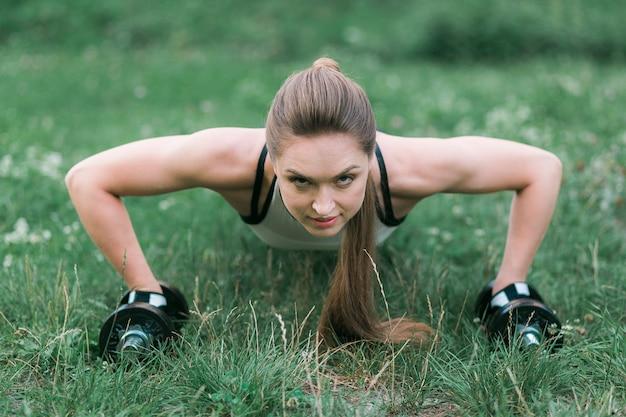 Bela morena slim fazendo push ups treino na grama verde no parque
