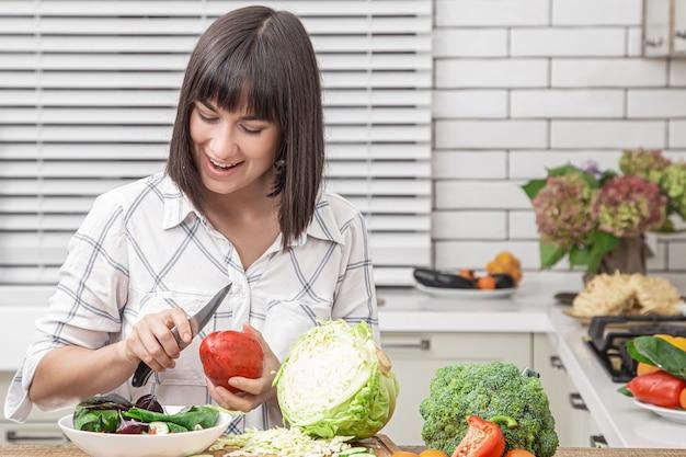 Bela morena sorri e corta legumes em uma salada na parede do interior de uma cozinha moderna.