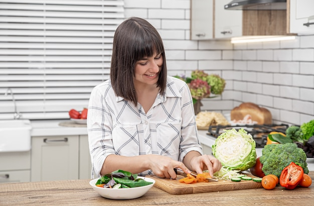 Bela morena sorri e corta legumes em uma salada no espaço do interior de uma cozinha moderna.