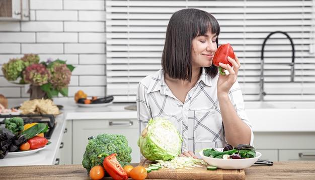 Bela morena sorri e corta legumes em uma salada no fundo do interior de uma cozinha moderna.