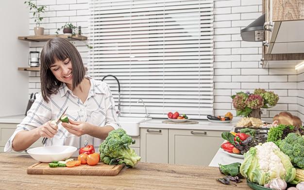 Bela morena sorri e corta legumes em uma salada no interior de uma cozinha moderna.