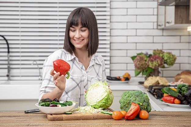 Bela morena sorri e corta o repolho para salada no interior da cozinha moderna.