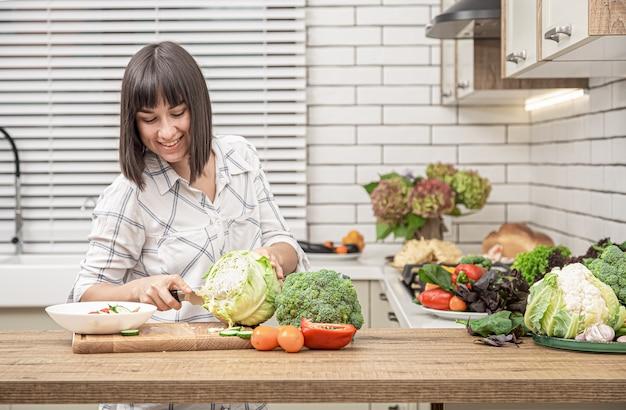 Bela morena sorri e corta repolho para salada no espaço do interior da cozinha moderna.