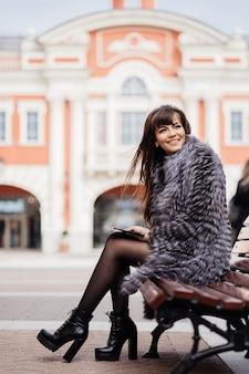 Bela morena sorridente com o cabelo longo e reto, vestindo um casaco de pele no contexto do edifício de estilo clássico, sentado no banco