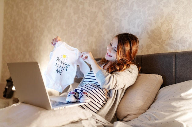 Bela morena sorridente com videochamada no laptop. mulher mostrando roupas de bebê que ela comprou. hora da noite.