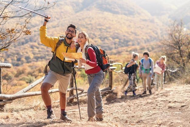 Bela morena sorridente segurando o mapa e olhando para o caminho certo enquanto homem apontando com vara. no fundo, o resto do grupo. caminhadas na natureza no conceito de outono.