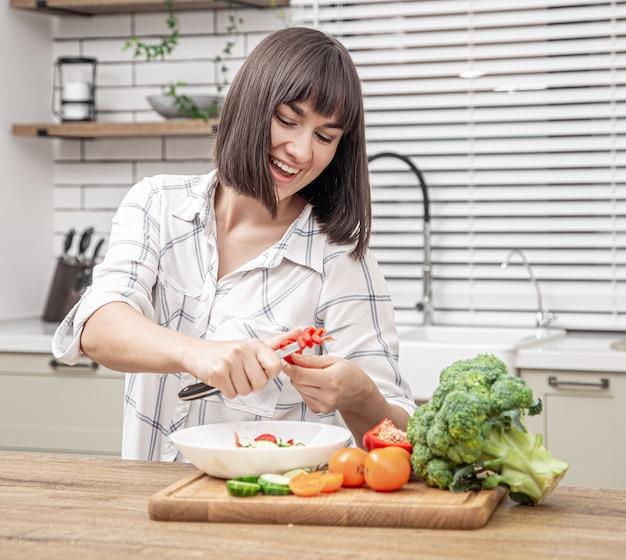 Bela morena sorrindo e preparando salada na parede borrada do interior da cozinha.