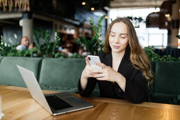 Bela morena usando laptop e celular no café. conceito de trabalho do blogger