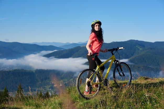 Bela motociclista feminina com bicicleta amarela nas montanhas de manhã. montanhas nebulosas, florestas. atividade esportiva ao ar livre