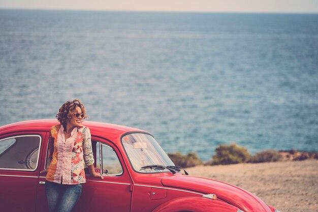 Bela motorista caucasiana de meia-idade posa em pé com um lendário carro vintage retrô vermelho atrás