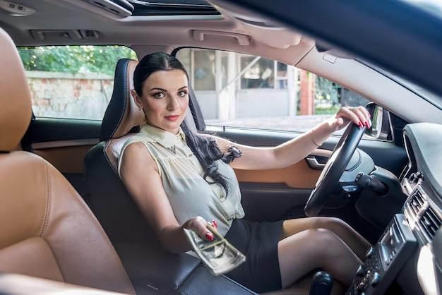 Bela motorista oferecendo um monte de dólares, sentada no carro