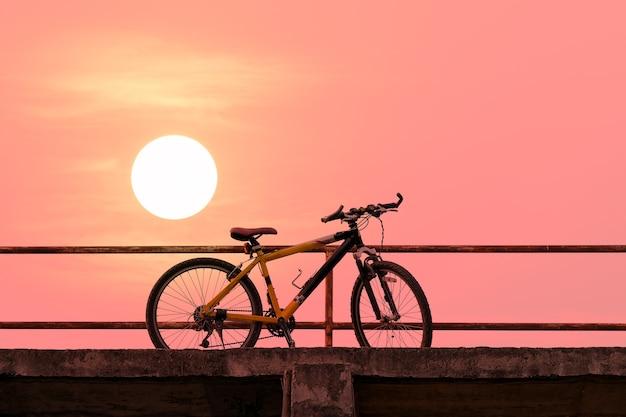 Bela mountain bike na ponte de concreto com luz solar colorida.