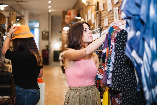 Bela mulher à procura de roupas novas