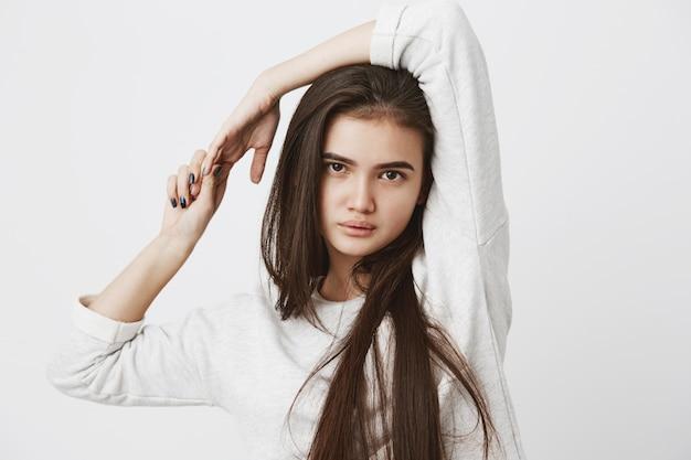 Bela mulher adolescente com cabelos longos escuros soltos, posando dentro de casa, vestida casualmente
