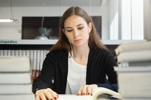 Bela mulher adolescente com cabelos longos morena vestindo uniforme estudando livro ou manual, ouvindo sua música favorita com fones de ouvido enquanto está sentado na biblioteca da escola