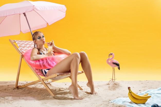 Bela mulher bebendo coquetel frio fresco, sentado na espreguiçadeira