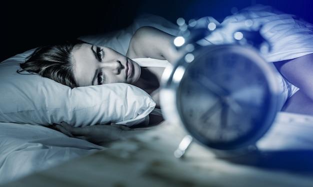 Bela mulher caucasiana insone e desesperada acorda à noite sem conseguir dormir,