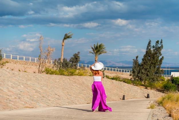 Bela mulher com chapéu e saia rosa