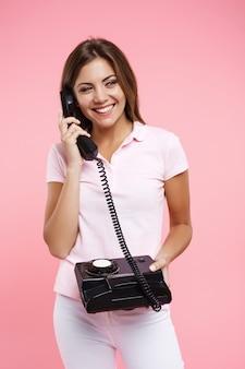 Bela mulher com roupa casual brilhante fazendo chamadas telefônicas e sorrindo