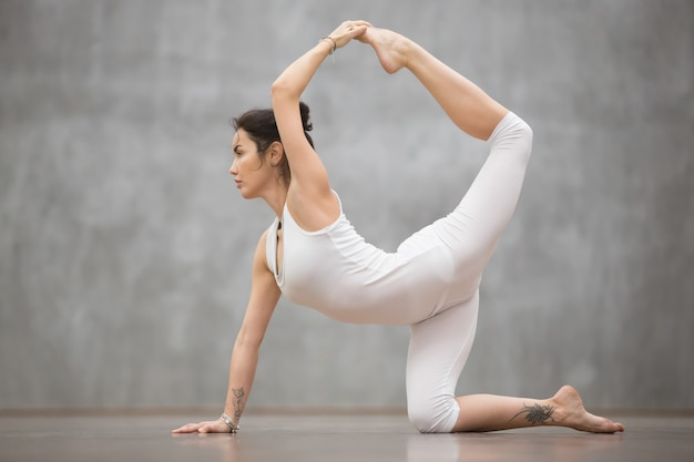 Bela mulher de iogue fazendo pose de chakravakasana