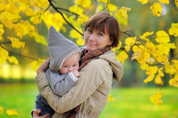 Bela mulher de meia idade e seu adorável netinho no parque outono