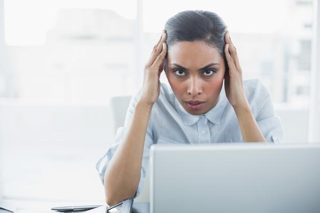 Bela mulher de negócios severa sentada em sua mesa enquanto sofria de dor de cabeça