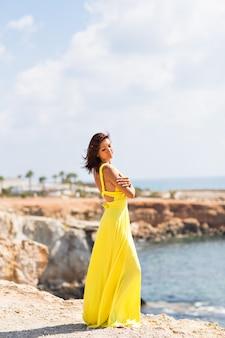 Bela mulher de vestido amarelo na praia.