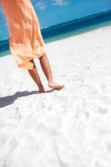 Bela mulher de vestido andando perto do oceano da praia em dia de verão na areia branca