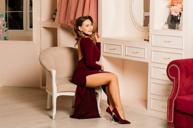 Bela mulher de vestido vermelho, quarto decorado para o natal. mulher no belo estúdio, ano novo.