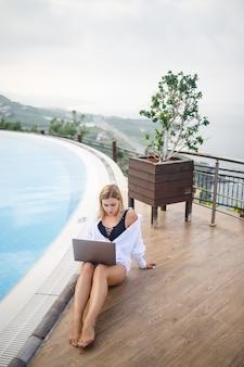 Bela mulher jovem e atraente se senta perto de uma grande piscina e trabalha em um laptop. trabalho remoto durante as férias.