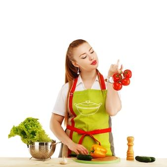 Bela mulher jovem sexy cozinhando uma refeição fresca contra branco.