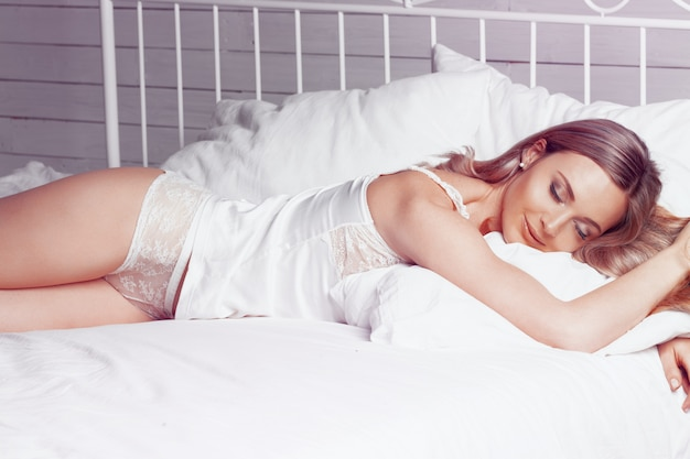Bela mulher linda noiva com um corpo sexy deitada na cueca na cama branca