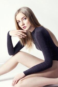 Bela mulher loira sexy. menina sentada no chão