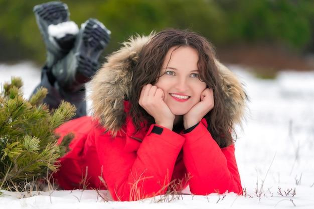 Bela mulher morena com cabelo longo cacheado encontra-se na neve do inverno na floresta de coníferas, sorrindo e olhando para o lado. jovem mulher branca vestida com uma jaqueta vermelha à prova de vento e botas de trekking.
