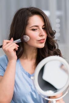 Bela mulher morena com pincel e espelho fazendo maquiagem