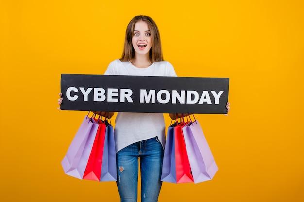 Bela mulher morena com sacolas coloridas e copyspace texto cyber segunda-feira assinar banner isolado sobre amarelo