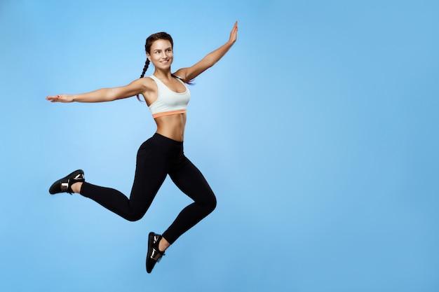 Bela mulher no sportswear legal pulando alto com as mãos para cima