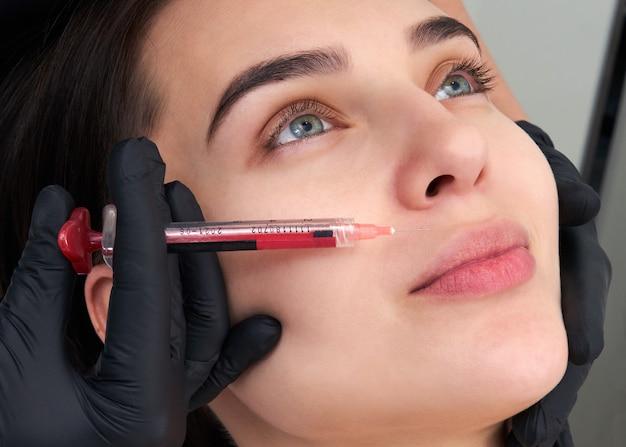 Bela mulher recebe uma injeção na cara dela