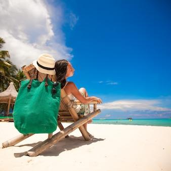 Bela mulher relaxante na cadeira de madeira na praia branca