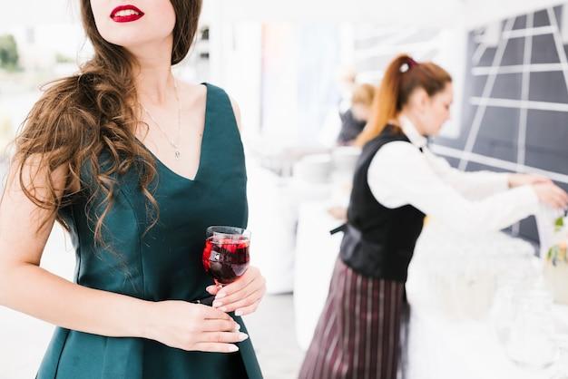 Bela mulher segurando o copo com álcool