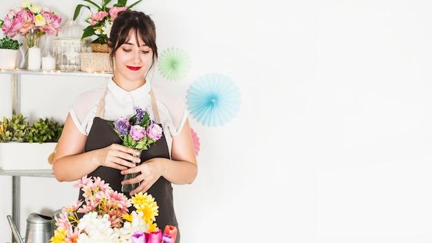 Bela mulher segurando o vaso de flores frescas na loja floral