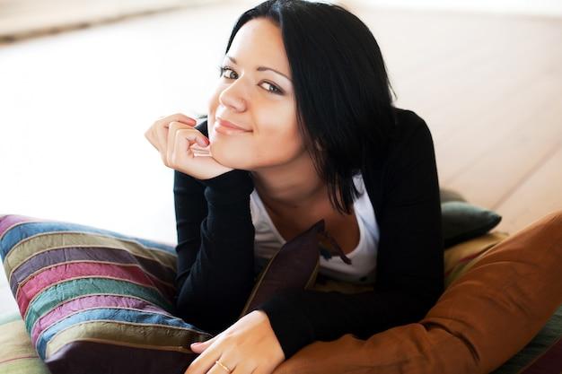 Bela mulher sentada e sorrindo dentro de casa
