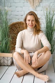 Bela mulher sentada em casa no chão de madeira