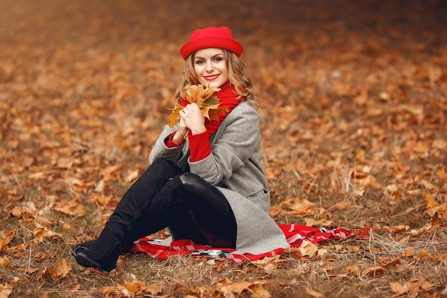 Bela mulher sentada em um parque de outono