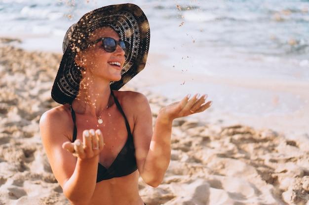 Bela mulher sentada na areia pelo oceano