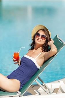 Bela mulher sentada na espreguiçadeira um cocktail