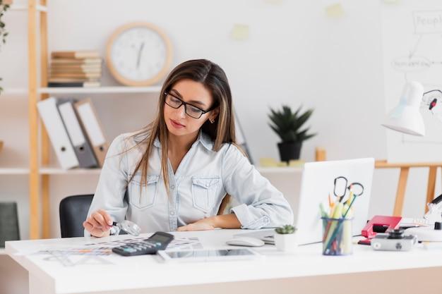 Bela mulher sentada no escritório e segurando uma lupa